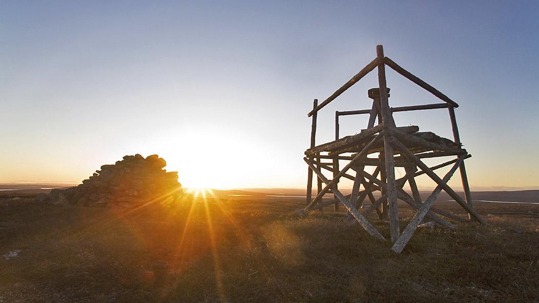 Puinen torni ja ihmisen kasaama kiviröykkiö tunturin laella. Horisontissa hohtaa laskeva aurinko joka värjää maiseman ilta-auringon sävyihin.