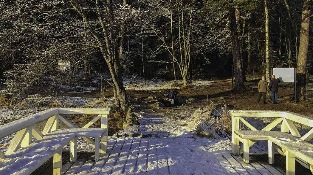 Lumen peittämä laituri. Taustalla kaksi retkeilijää tutkivat opastaulua metsän edustalla.