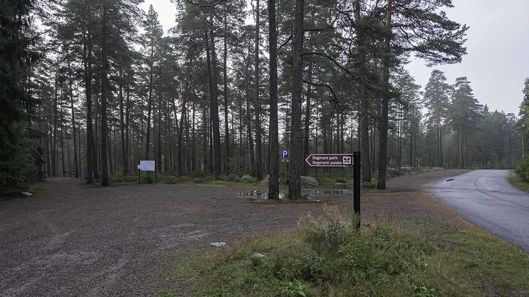 Pysäköintialue ja sen vieressä autotie. Taustalla metsää.